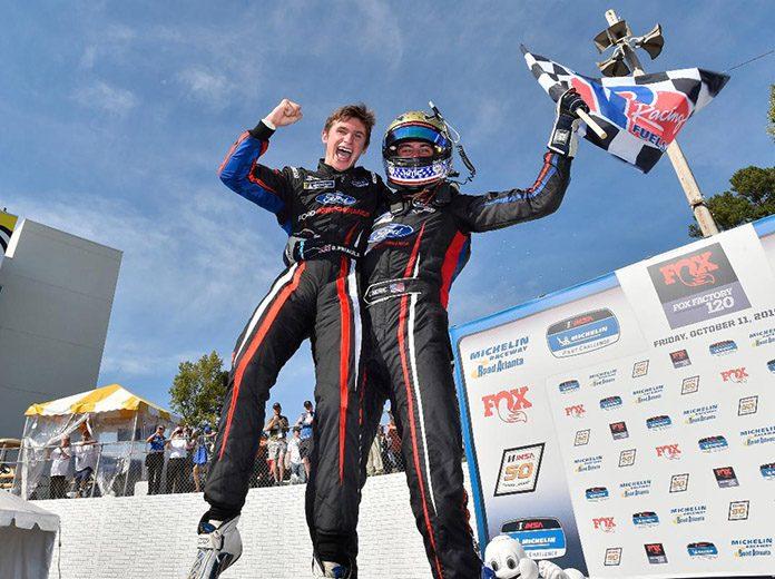 Seb Priaulx (left) and Austin Cindric celebrate after a victory in Friday's IMSA Michelin Pilot Challenge event at Michelin Raceway Road Atlanta. (IMSA Photo)