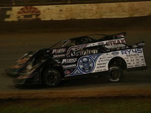 Teammates Scott Bloomquist (0) and Chris Madden (0M) battle it out Friday night at The Dirt Track at Charlotte. (Dallas Breeze Photo)