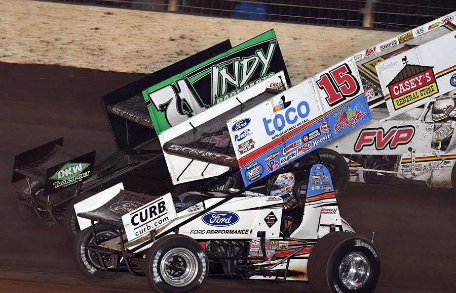 Donny Schatz (15) races under Gio Scelzi during Saturday's World of Outlaws NOS Energy Drink Sprint Car Series finale at The Dirt Track at Charlotte. (Frank Smith Photo)