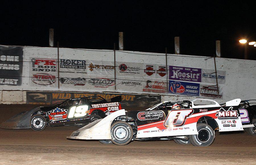 Rick Eckert (0) battles under Ryan Gustin during Wednesday's Wild West Shootout event at Arizona Speedway. (Mike Ruefer Photo)