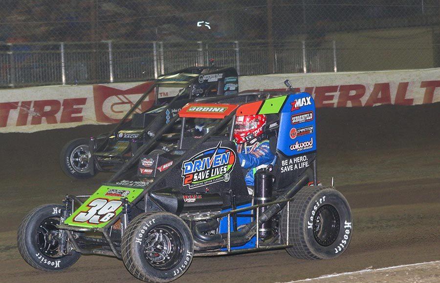 Cole Bodine (39) races under Logan Seavey during Thursday's Chili Bowl qualifying feature at Tulsa Expo Raceway. (Brendon Bauman Photo