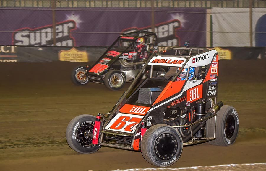 Holley Hollan (67) races under Jason Martin during preliminary action on Thursday at the Chili Bowl. (Mark Coffman Photo)