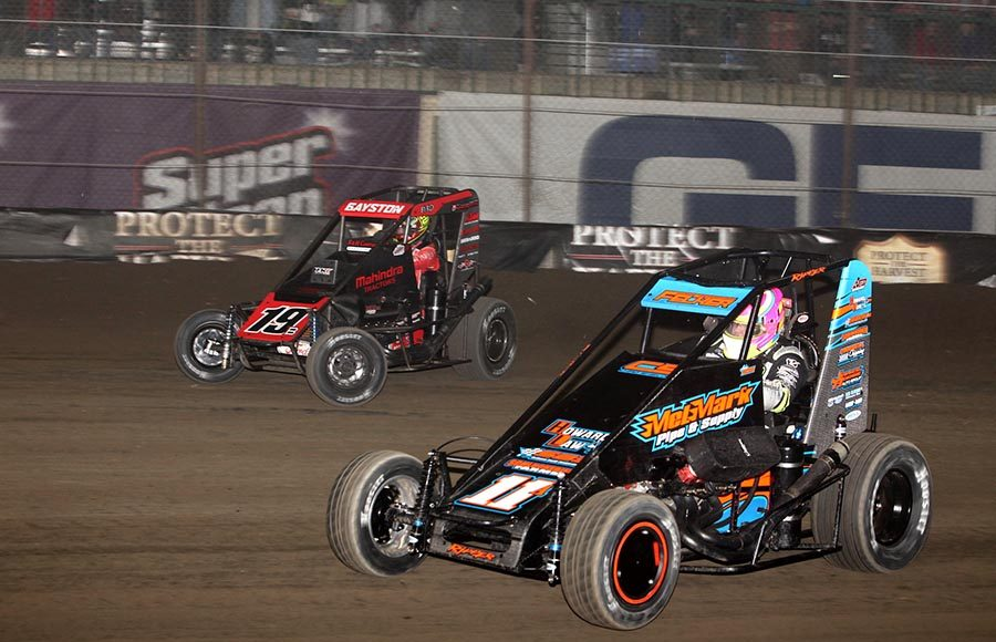 Andrew Felker (11) races under Spencer Bayston during Thursday's Chili Bowl preliminary feature at Tulsa Expo Raceway. (Richard Bales Photo)