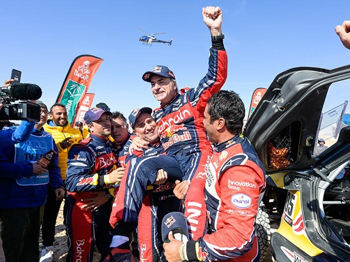 Carlos Sainz gets lifted in the air after clinching his third Dakar Rally title. (Dakar Rally Photo)