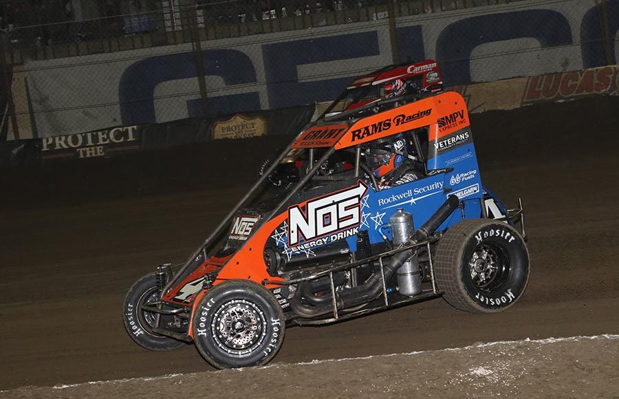 Justin Grant (4) races alongside Daryn Pittman during Friday's Chili Bowl qualifying event at Tulsa Expo Raceway. (Brendon Bauman Photo)