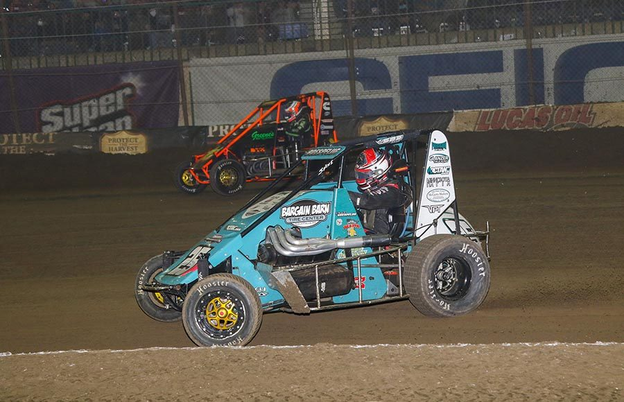 Chad Boespflug (25) races alongside A.J. Hopkins during Friday's Chili Bowl qualifying event at Tulsa Expo Raceway. (Brendon Bauman Photo)
