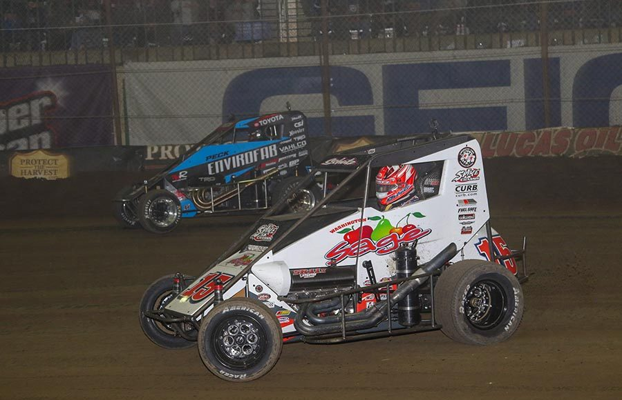 Donny Schatz (15) races under Justin Peck during Friday's Chili Bowl qualifying event at Tulsa Expo Raceway. (Brendon Bauman Photo)