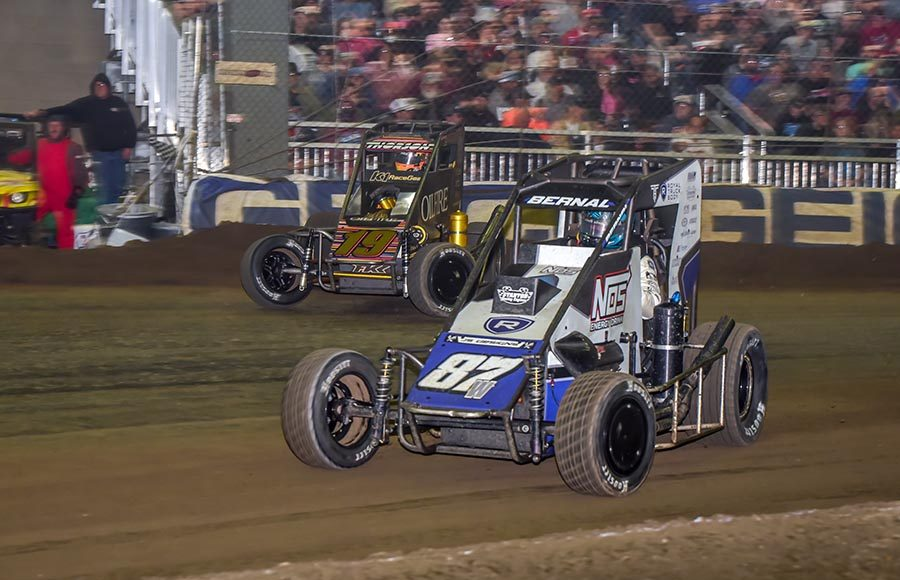Ryan Bernal (87) battles Tanner Thorson for the race lead during Friday's Chili Bowl preliminary event at Tulsa Expo Raceway. (Mark Coffman Photo)