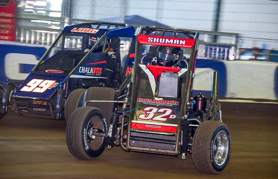 Casey Shuman (32) races under Brandon Long during the alphabet soup portion of the Chili Bowl on Saturday at Tulsa Expo Raceway. (Mark Coffman Photo)