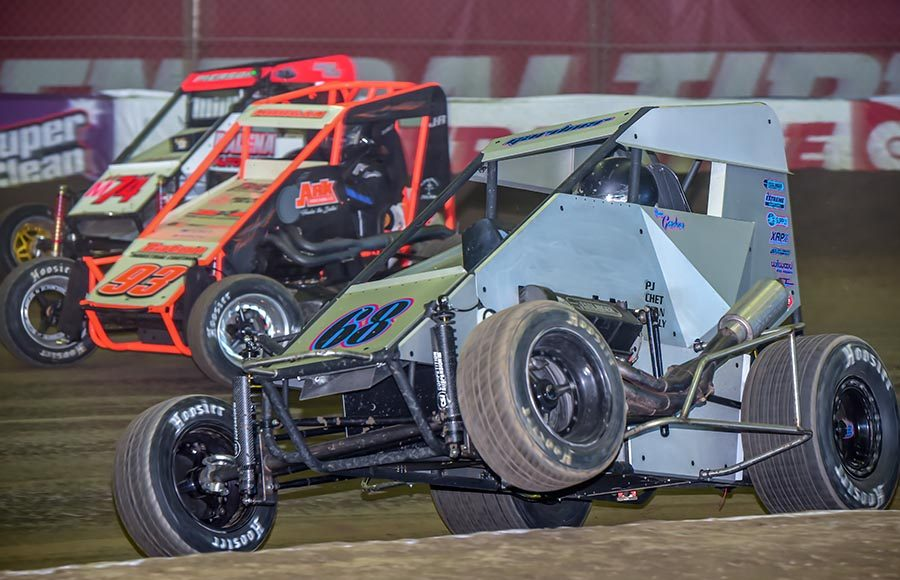 Ronnie Gardner (68) pops a wheelie as he battles Dustin Morgan (93) and Adam Pierson during the alphabet soup portion of the Chili Bowl on Saturday at Tulsa Expo Raceway. (Mark Coffman Photo)