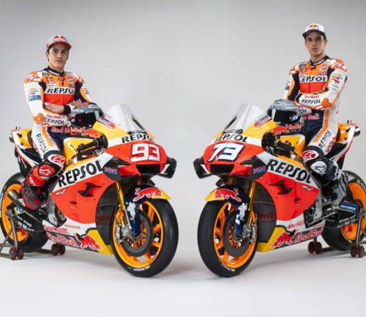 Brothers Marc and Alex Marquez sit aboard their Repsol Honda bikes.