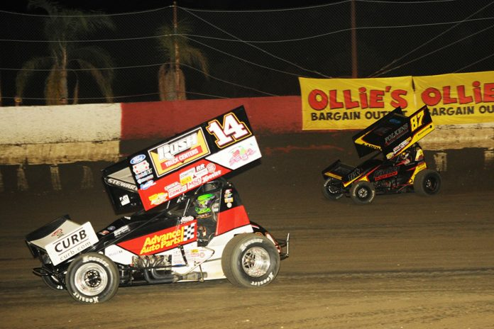 Tony Stewart (14) races ahead of Aaron Reutzel during Monday's Ollie's Bargain Outlet All Star Circuit of Champions main event at East Bay Raceway Park. (Julia Johnson Photo)