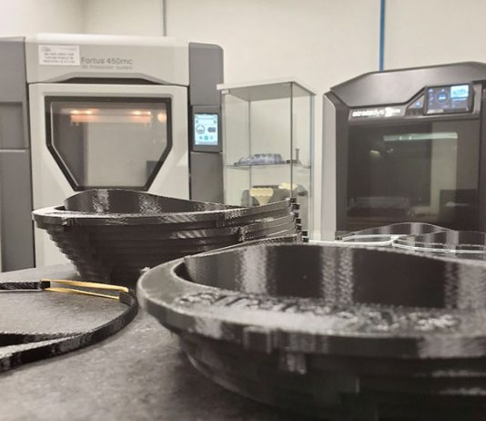 Don Schmuacher Motorsports' two Stratasys FDM 3D printers (background) are operating around-the-clock to produce headbands to be used as part of medical face shields.