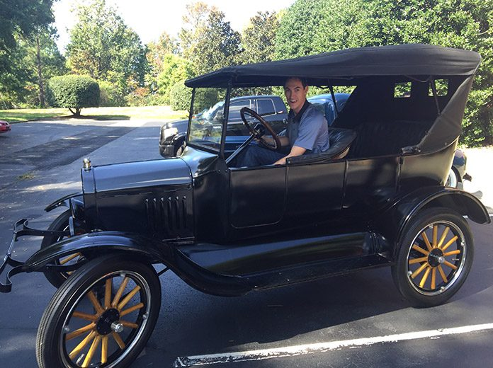 Joey Logano sits aboard his vintage Model T Ford