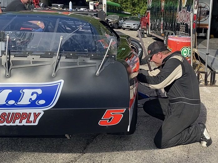 Casey Johnson works on his race car in the pits Sunday afternoon at Slinger Super Speedway. (Nick Dettmann Photo)