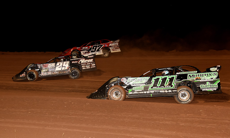 Darrell Lanigan (29), Cade Dillard (97) and Max Blair battle for the race lead during Saturday's Firecracker 100 finale at Lernerville Speedway. (Paul Arch Photo)