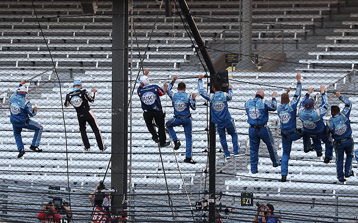 Kevin Harvick and his crew celebrate by climbing the fence at Indianapolis Motor Speedway after winning Sunday's Big Machine Hand Sanitizer 400. (Chris Graythen/Getty Images Photo)