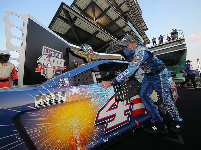 Rodney Childers, crew chief of the No. 4 Busch Light Patriotic Ford driven by Kevin Harvick, pushes the car from victory lane after winning the Big Machine Hand Sanitizer 400 Sunday at Indianapolis Motor Speedway. (Chris Graythen/Getty Images Photo)