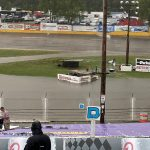 A fan picks up his chair after heavy rain and gusting winds went through the area Tuesday evening ahead of the 41st SUPERSEAL Slinger Nationals presented by Miller Lite at Slinger Super Speedway in Slinger, Wis. The race was postponed to Wednesday. (Nicholas Dettmann Photo)