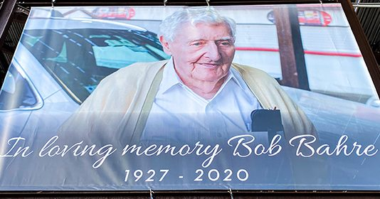 A banner on the Main Grandstand is just one way the late track founder and New England motorsports pioneer, Bob Bahre, is being honored during the NASCAR Cup Series Foxwoods Resort Casino 301 at New Hampshire Motor Speedway this weekend. (NHMS Photo)
