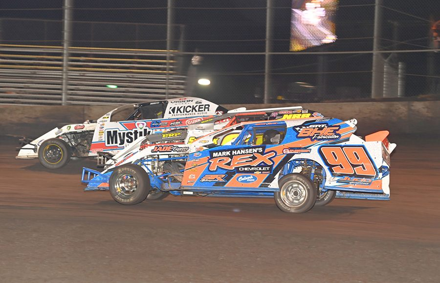 Rocky Caudle (99) and Cam Reimers (21) split another car during Northern sportmod action Wednesday at the IMCA Super Nationals at Boone Speedway. (Tom Macht Photo)