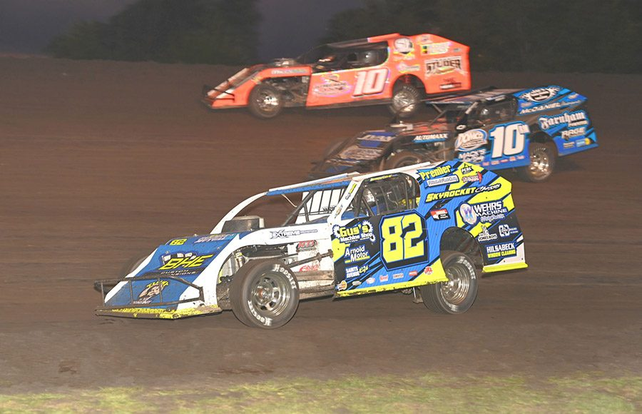 Modified racers battle three-wide during the IMCA Speedway Motors Super Nationals fueled by Casey's at Boone Speedway. (Tom Macht Photo)