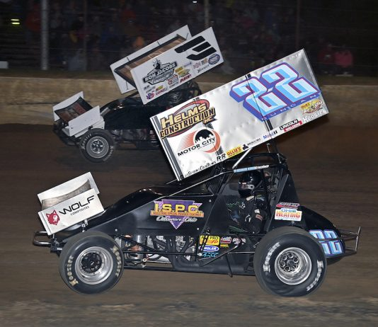 Cole Duncan (22) races under Jac Haudenschild at Atomic Speedway. (Mike Campbell photo)