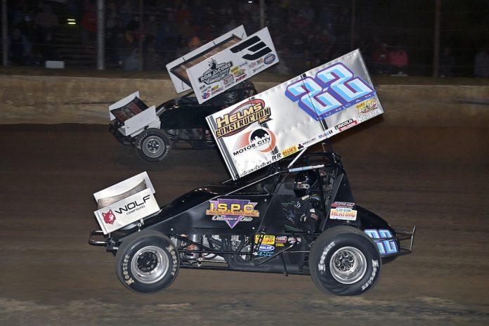 Cole Duncan (22) races under Jac Haudenschild at Atomic Speedway. (Mike Campbell photo)