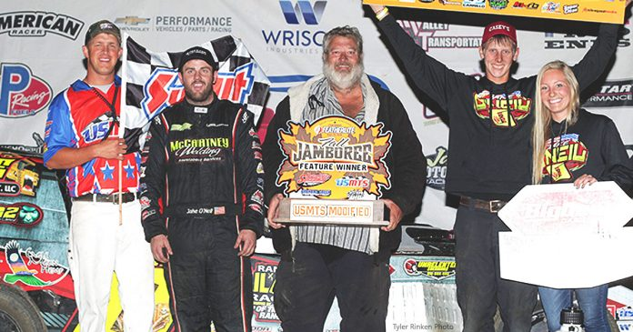 Jake O'Neil poses in victory lane with his team after winning Friday's Featherlite Fall Jamboree opener at Deer Creek Speedway.