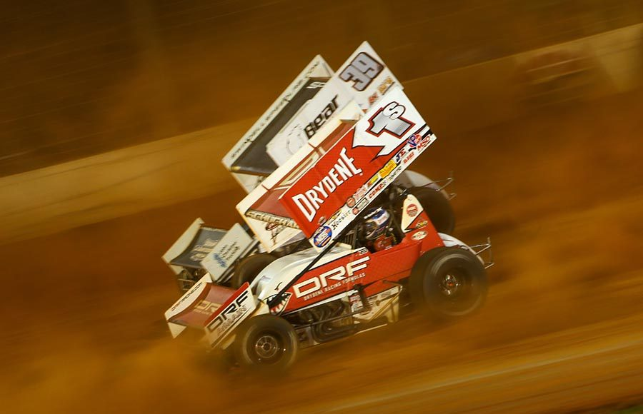 Logan Schuchart (1s) races under Spencer Bayston during Friday's World of Outlaws NOS Energy Drink Sprint Car Series event at The Dirt Track at Charlotte. (Adam Fenwick Photo)