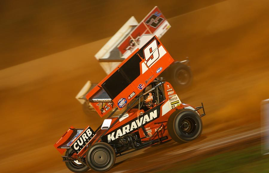 James McFadden (9) races under Wayne Johnson during Friday's World of Outlaws NOS Energy Drink Sprint Car Series event at The Dirt Track at Charlotte. (Adam Fenwick Photo)