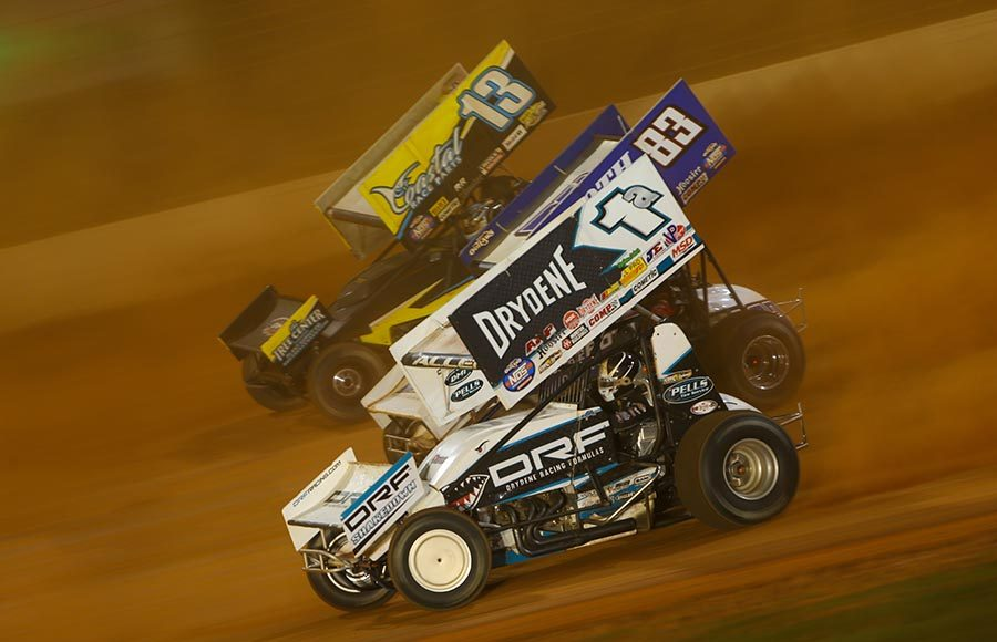 Jacob Allen (1a), Dominic Scelzi (83) and Justin Peck battle for position during Saturday's World of Outlaws NOS Energy Drink Sprint Car Series event at The Dirt Track at Charlotte. (Adam Fenwick Photo)