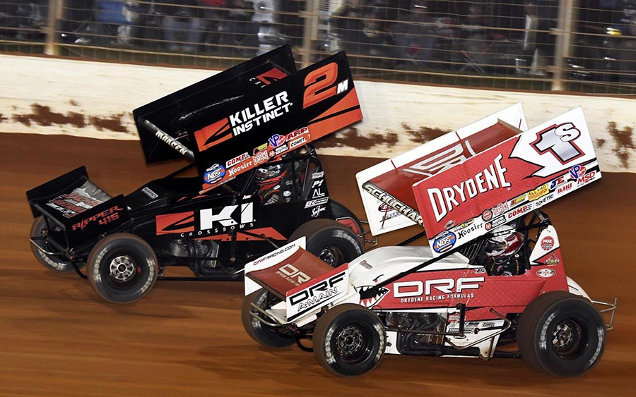 Logan Schuchart (1s) races under Kerry Madsen during Saturday's World of Outlaws NOS Energy Drink Sprint Car Series event at The Dirt Track at Charlotte. (Frank Smith Photo)
