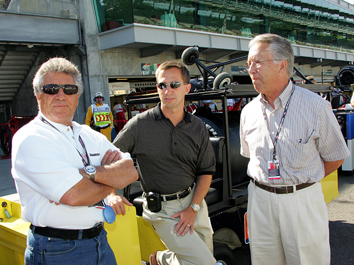 Aldo Andretti (right) stands on the Indianapolis Motor Speedway with his son John Andretti (center) and twin brother Mario Andretti (left). (IndyCar photo)