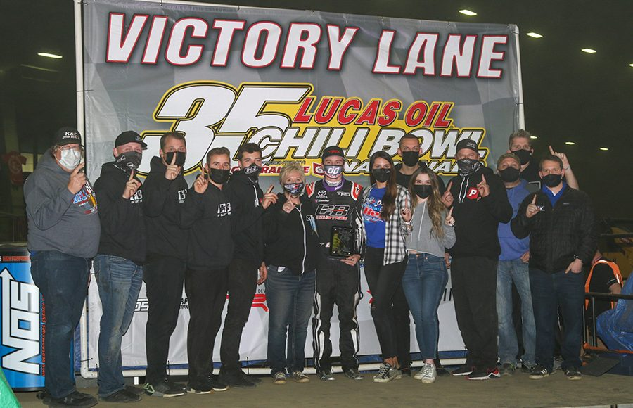 Christopher Bell poses in victory lane with his team after winning Thursday's Chili Bowl qualifying feature. (Brendon Bauman Photo)