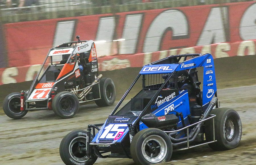 Andrew Deal (15) races under Kaylee Bryson during Thursday's Chili Bowl preliminary feature. (Brendon Bauman Photo)