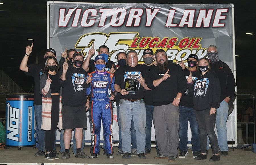 Justin Grant poses in victory lane with his crew after winning Friday's Chili Bowl preliminary feature. (Brendon Bauman Photo)