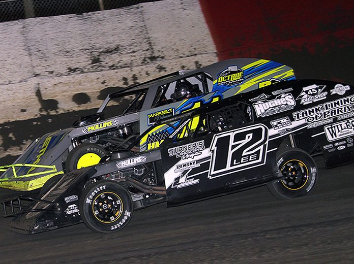 Lucas Lee (12) races under Spencer Hughes during Thursday's DIRTcar UMP Modified feature at East Bay Raceway Park. (Jim Denhamer Photo)