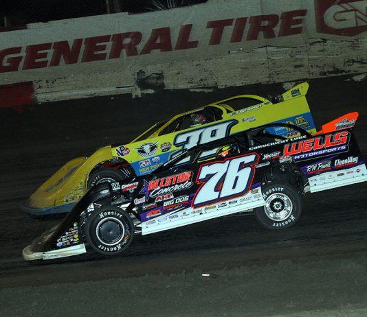 Brandon Overton (76) races under Tim McCreadie Friday night at East Bay Raceway Park. (Jim DenHamer photo)