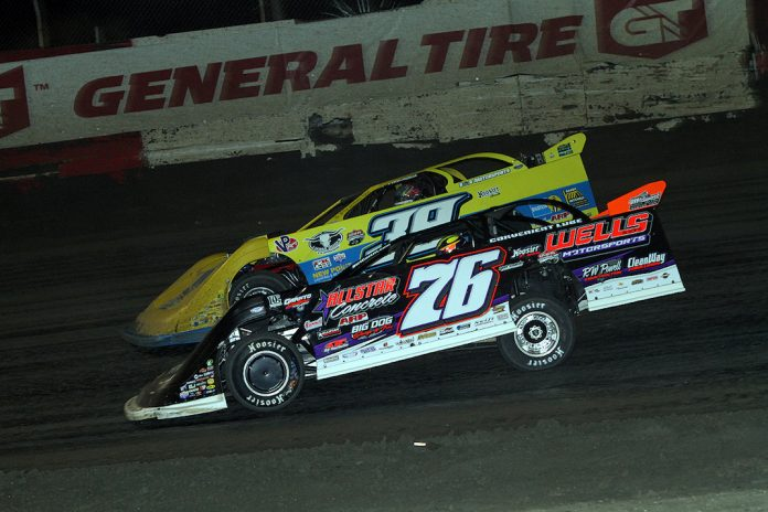 Brandon Overton (76) races under Tim McCreadie Friday night at East Bay Raceway Park. (Jim DenHamer photo)