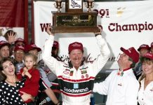 HAMPTON, GA - NOVEMBER 17: Driver Dale Earnhardt holds up the Winston Cup trophy after winning the championship for 1991 on November 17, 1991 at the Atlanta International Raceway in Hampton , Georgia. With Dale are his wife Teresa holding daughter Taylor and T. Wayne Roberts of RJR. (Photo by Dozier Mobley/Getty Images)