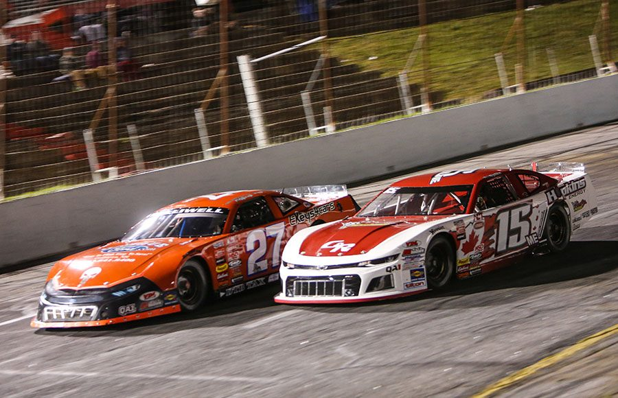 Mike Hopkins (15) battles Wayne Helliwell Jr. for the race lead during Friday's American-Canadian Tour event at Hickory Motor Speedway. (Adam Fenwick Photo)