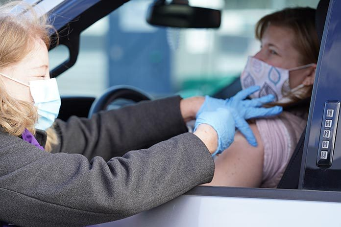 A patient receiving the COVID-19 vaccine from a volunteer at New Hampshire's second vaccine super site at New Hampshire Motor Speedway on Saturday, March 27. (NHMS/Vinny Orest Photo)
