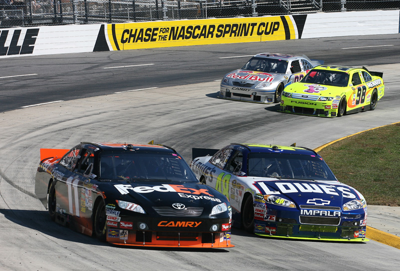 SIDE BY SIDE: Denny Hamlin (11) and Jimmie Johnson fight for track position during the NASCAR Sprint Cup Series Tums Fast Relief 500 at Martinsville (Va.) Speedway. (HHP/Harold Hinson Photo)