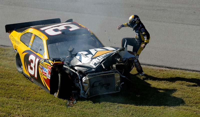 MAN AND MACHINE: A frustrated Jeff Burton kicks his Chevrolet after a late-race crash with Dale Earnhardt, Jr. during Sunday's NASCAR Sprint Cup Series Amp Energy Juice 500. (John Harrelson/Getty Images Photo)
