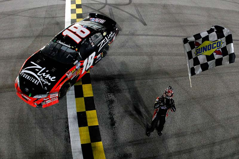DROPPING THE CHECKERS: Kyle Busch prepares to catch the checkered flag after winning the Ford 300 NASCAR Nationwide Series race Saturday at Florida's Homestead-Miami Speedway. (Todd Warshaw/Getty Images Photo)