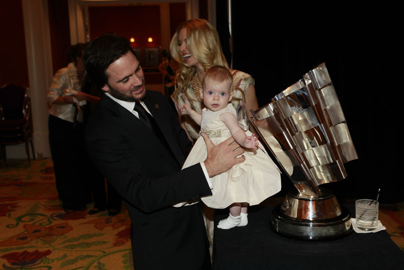 FAMILY MAN: Jimmie Johnson holds his daughter Genevieve up next to his Sprint Cup trophy Friday night. (Chris Trotman/Getty Images Photo)