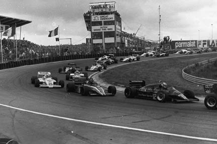 The field files into the first turn at the start of the 1983 Dutch Grand Prix at the famed Zandvoort road course.