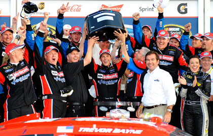 Trevor Bayne hoists the Harley J. Earl Trophy in victory lane. (Jared C. Tilton/Getty Images Photo)