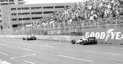 Fans in temporary grandstands watch the field file past during the 1990 United States Grand Prix Formula One race held on the streets of Phoenix.